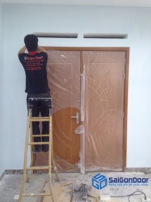 Nhân viên lắp đặt Cửa Gỗ Sài Gòn đang hoàn thiện bước cuối cùng